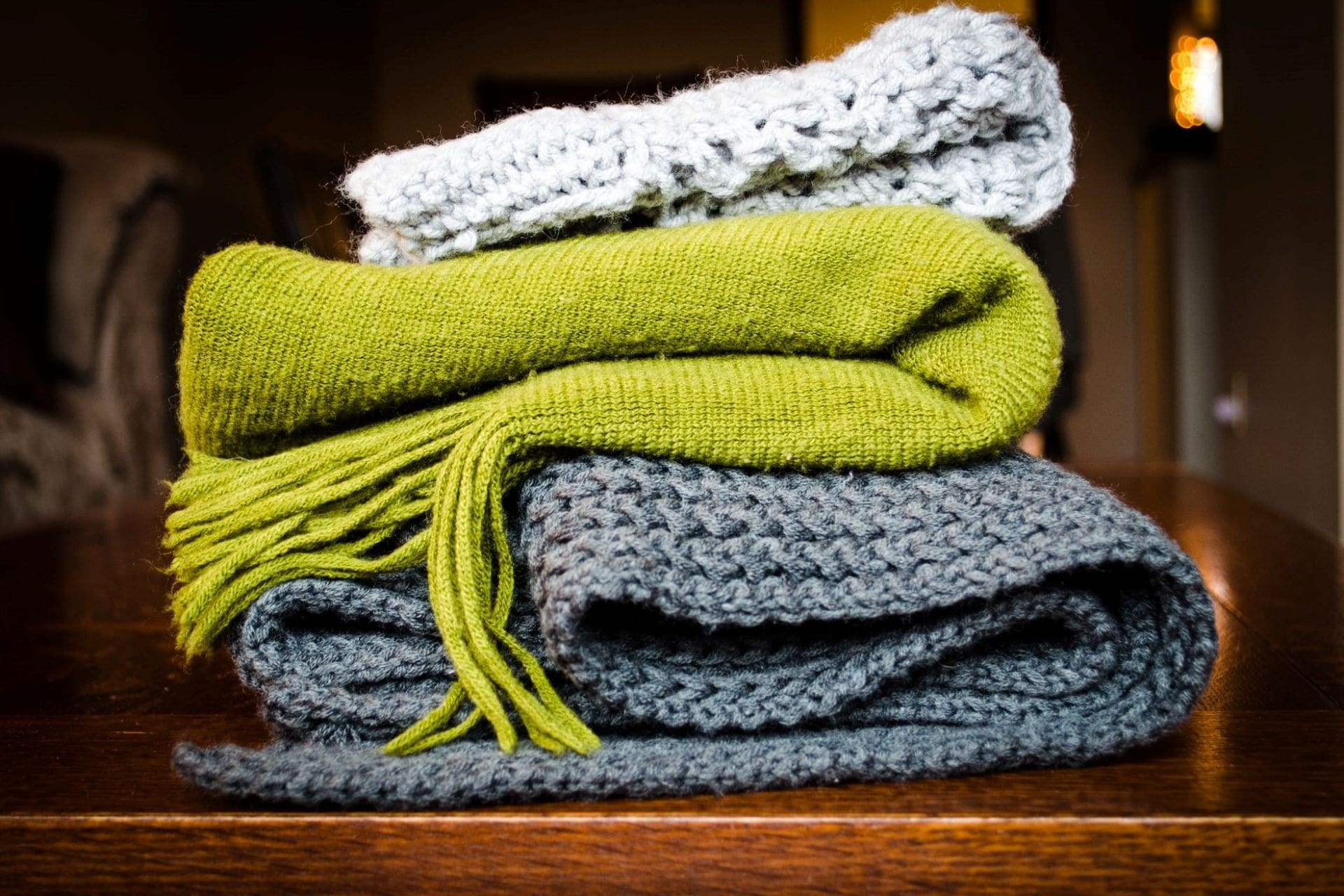 warm-woolen-knitted-scarves-folded-up-on-table-cheapest-ways-to-heat-a-house